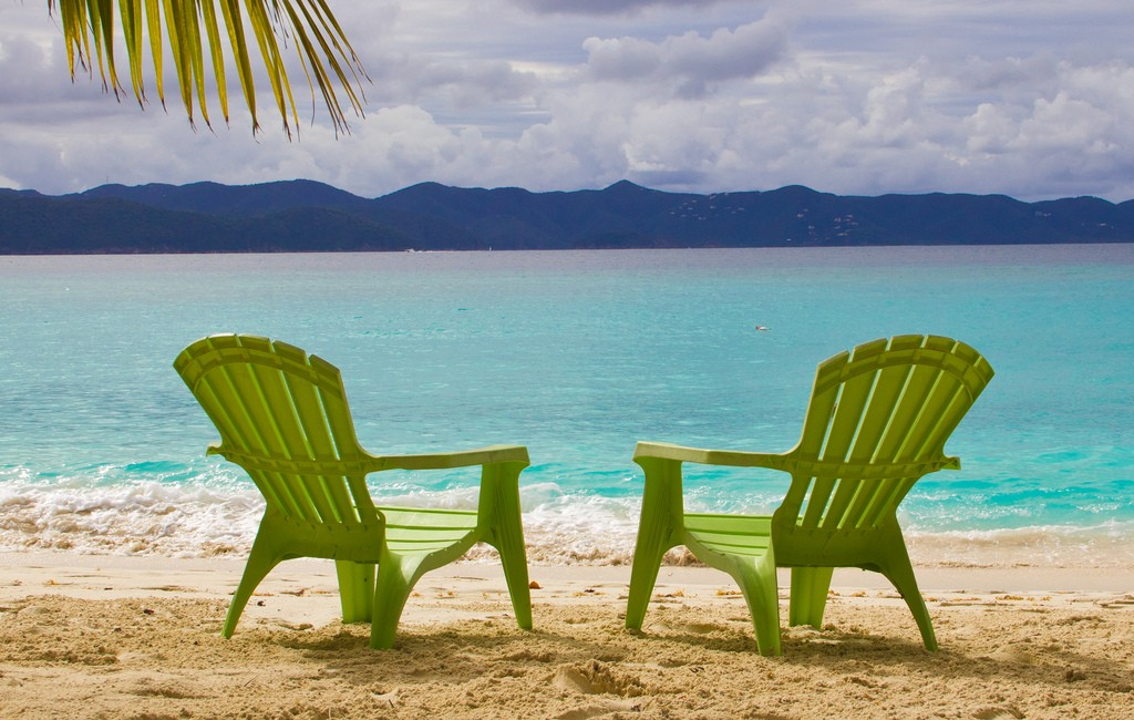 Beach chairs under a palm tree in the BVI. Image by Ken Teegardin.